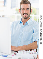 Portrait of a smiling young man using computer