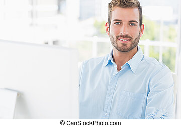 Smiling young man using computer in