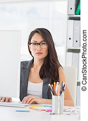 Serious young woman using computer in office - Portrait of a...