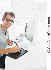 Side view of a casual male photo editor using graphics tablet
