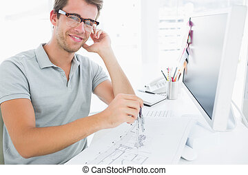 Man using compass on design - Smiling young man using...