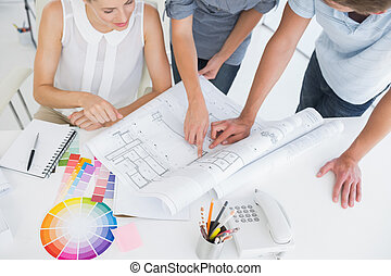 High angle view mid section of artists working on designs in...