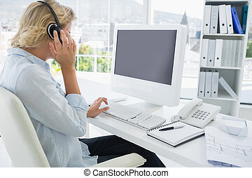 Casual young woman with headset using computer