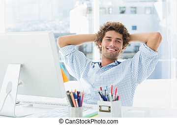 Casual young man with computer in a bright office - Relaxed...