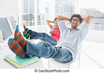 Relaxed casual couple with legs on desk in office - Portrait...