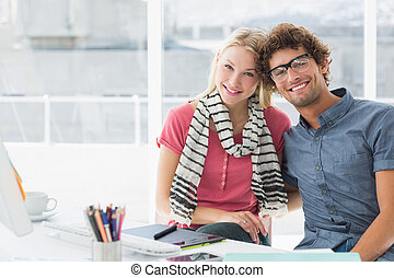Portrait of a smiling casual business couple sitting in a...