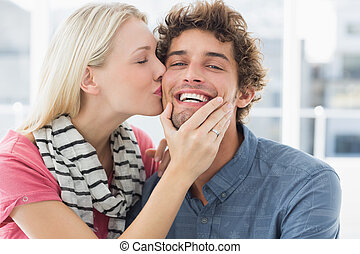 Woman kissing man on his cheek - Happy casual young woman...
