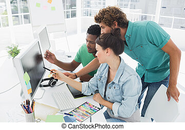 Three artists working on computer at office - Side view of...