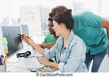 Three artists working on computer at office