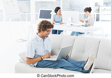 Man using laptop with colleagues at creative office