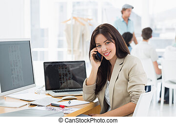 Woman on call at desk with colleagues behind in office -...