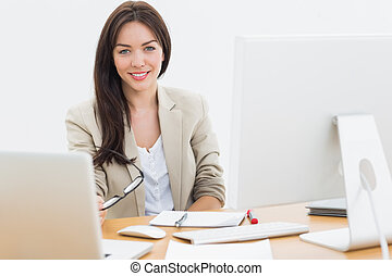 Young woman with computers at desk in office - Portrait of a...