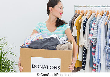 Woman with clothes donation - Smiling young woman with...