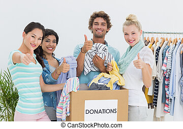 People with clothes donation gesturing - Group of young...