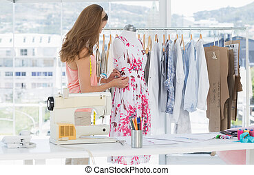 Female fashion designer working on floral dress - Side view...