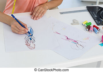 Mid section of a fashion designer working on her designs -...