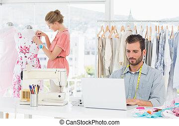 Man using laptop with fashion designer working at studio -...