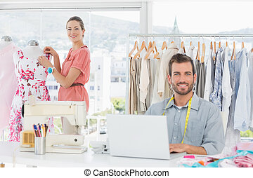 Man using laptop with fashion designer working at studio