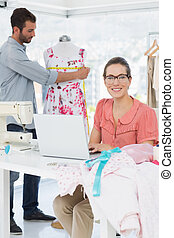 Woman using laptop with fashion designer working at studio
