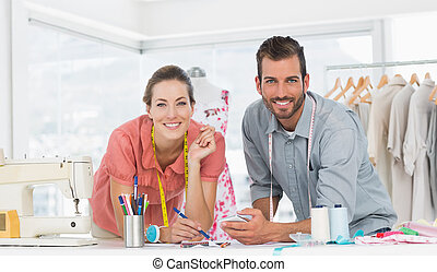 Fashion designers at work in bright studio - Male and female...