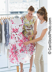 Young women shopping in clothes store - Two happy young...