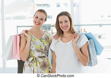 Happy women with shopping bags in clothes store - Portrait...