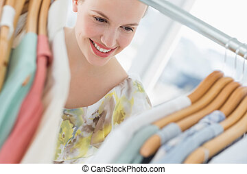 Beautiful female customer selecting clothes at store -...