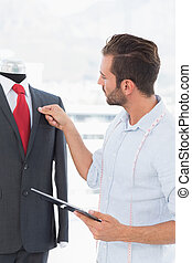 Fashion designer with digital tablet looking at suit on...