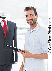 Fashion designer with digital tablet by suit on dummy -...