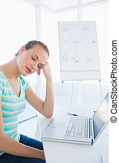 Casual woman sleeping in front of laptop at office
