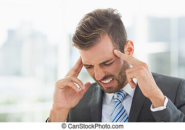 Close-up of a young businessman with headache