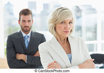 Mature businesswoman and young man with arms crossed -...
