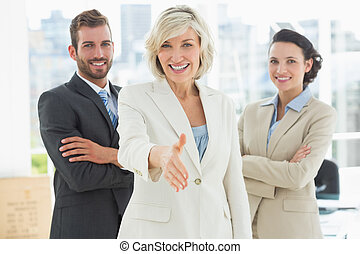 Confident businesswoman offering handshake with team -...