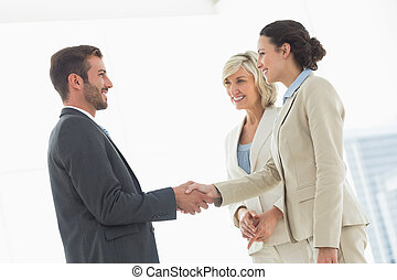 Executives shaking hands after a business meeting - Side...