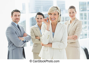 Mature businesswoman wearing headset with colleagues in office