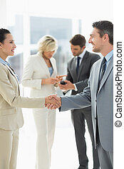 Executives shaking hands in office - Executives shaking...