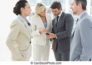 Business colleagues in discussion during office break -...