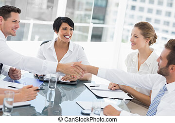 Executives shaking hands during a business meeting - Side...