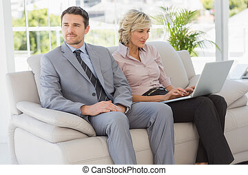 Well dressed man with woman using laptop at home - Well...