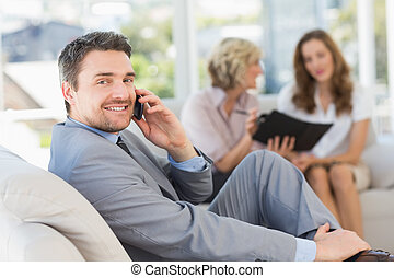 Businessman on call with female colleagues in background -...