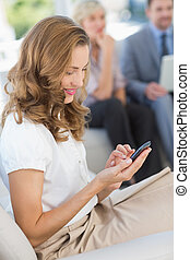 Businesswoman text messaging with colleagues using laptop in...