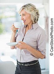 Smiling beautiful businesswoman drinking tea in office -...