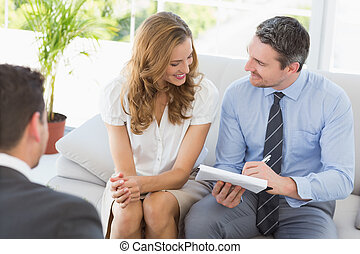 Smiling couple in meeting with a financial adviser - Smiling...