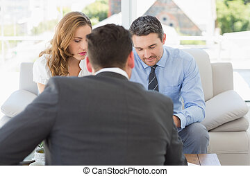 Couple in meeting with a financial adviser at home - Young...