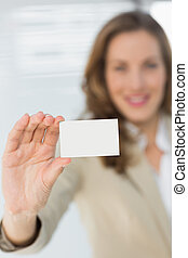 Smiling businesswoman holding blank card