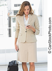 Businesswoman text messaging while on a business trip -...
