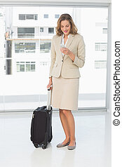 Businesswoman text messaging while on a business trip - Full...