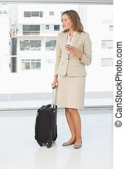 Businesswoman text messaging while on business trip - Full...