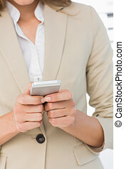 Mid section of a businesswoman text messaging - Close-up mid...