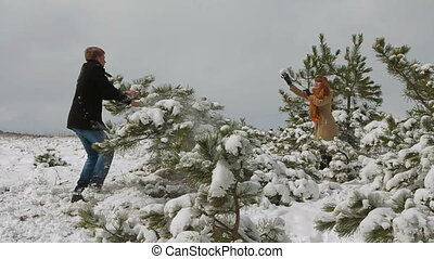 Snowball fight. Slow motion - Man and woman playing...